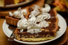 Scharfer Kuchen der Schokolade mit Nüssen und Schlagsahne auf die Oberseite lizenzfreie stockbilder