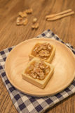 Scharfer Nachtisch der frischen köstlichen Karamellnuß auf hölzerner Platte Stockfotografie