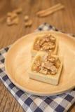 Scharfer Nachtisch der frischen köstlichen Karamellnuß auf hölzerner Platte Lizenzfreie Stockfotos