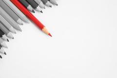 Scharfer rote Farbbleistiftstand aus anderen Bleistiften heraus Stockfotografie