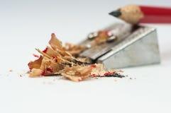 Scharfer roter Bleistift, Bleistiftspitzer, Fokus auf dem Abfall Stockbilder