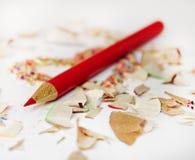 Scharfer roter Bleistift unter Bleistiftschnitzeln Stockbilder
