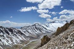 Scharfer Schnee bedeckte Gebirgsrücken mit Fluss und grünes Tal auf Unterseite Stockbilder
