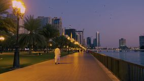 Scharjah, UAE - 10. Mai 2018: arabischer Mann, der auf Abenddamm Al Buheirah Corniche auf Hintergrundstadtpark geht und stock footage