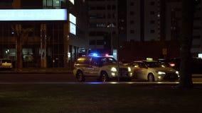 Scharjah, UAE - 10. Mai 2018: blaues und rotes Licht, das auf Spitzen- Polizeiwagen in Nacht-Scharjah-Stadt UAE blitzt Stadtautob stock video