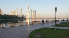 Scharjah, UAE - 10. Mai 2018: die arabischen Leute, die auf Morgendamm auf Hintergrund gehen, reflektierten Sonnenlicht im Glas stock footage