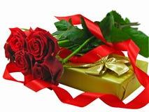 Scharlachrot Rosen mit dem goldenen Geschenkkasten. Lizenzfreie Stockbilder