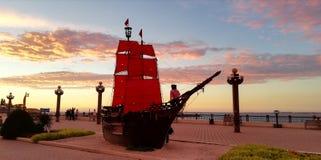 Scharlakansrött seglar på bakgrunden av en bedöva havssolnedgång arkivbilder