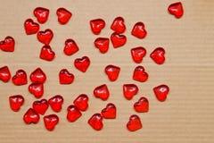 Scharlaken harten op kartonachtergrond Stock Foto's