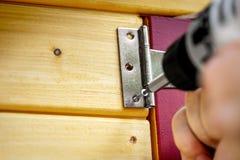 Scharnier-Türpassender oder Queraufhänger wird zu einer Tür geschraubt stockfoto