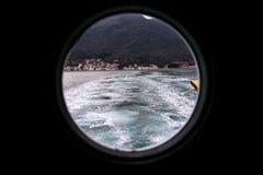 Scharnierend om venster, onweersdekking op schip die buiten in Middellandse Zee kijken Patrijspoortmening door venster op schip stock foto
