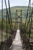 Scharnierende brug over bergrivier stock afbeelding