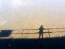 Schatten der alleinstellung der Person oder des Schattenbildes auf der Brücke und Reflexion auf dem Fluss Lizenzfreie Stockfotografie