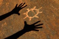 Schatten der Hände, die Sun-Petroglyphe anbeten Stockfotos