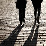 Schatten der Leute, die in eine Straße gehen Lizenzfreie Stockfotos