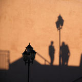 Schatten der Leute- und Straßenlaterne Stockbild
