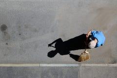 Schatten der Reinigungsstraße der alten Frau mit dem Besen Stockbild