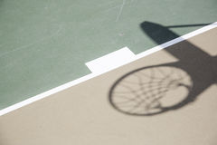 Schatten des Basketballkorbes und des Netzes gegen Gericht Stockfotografie