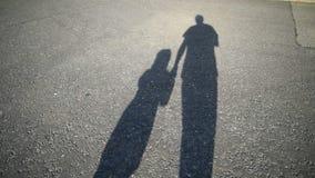 Schatten des Elternteils und des Kindes, die zusammen entlang Straße gehen stock footage