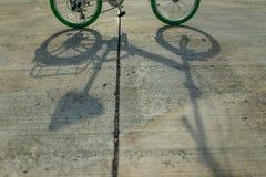 Schatten des Fahrrades auf der Straße Stockbilder
