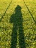 Schatten des Fotografen auf dem Gras Stockfotografie