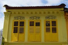 Schatten des Gelbs auf Kolonialfenstern und Fensterläden in wenigem Indien, Singapur Stockbild