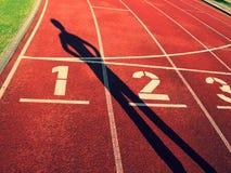 Schatten des Läufers Weiße Bahnzahl auf roter Gummirennbahn, Beschaffenheit von laufenden Rennbahnen Stockbilder