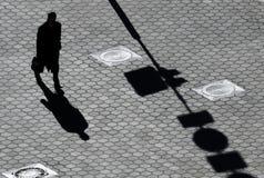 Schatten des Mannes auf Pflasterung Stockbilder