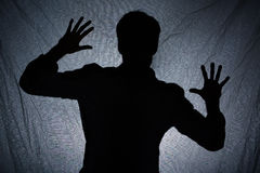 Schatten des Mannes hinter dunklem Gewebe Lizenzfreie Stockfotos