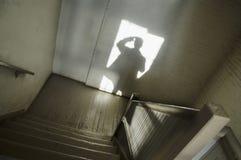 Schatten des Mannes im Treppenhausschacht Lizenzfreies Stockfoto