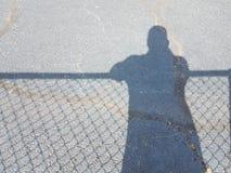 Schatten des Mannes mit Schatten des Zauns Stockfotografie