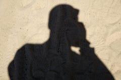 Schatten des Mannreisenden mit Rucksack machen Foto auf Sandstrand zur Sonnenuntergangzeit, Reise herein stockfotografie