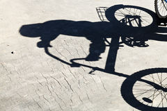 Schatten des Radfahrers auf Straße Stockbild