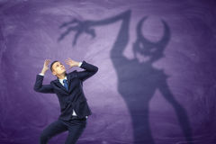 Schatten des Teufels versuchend, den erschrockenen Geschäftsmann zu fangen Lizenzfreie Stockfotografie