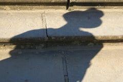 Schatten des tragenden Hutes der Person, auf Schritten Stockfoto