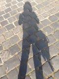 Schatten einer Frau auf Kopfstein Stockbild