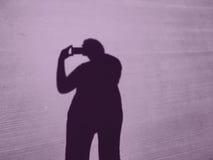 Schatten einer Frau mit einem iPhone macht Fotos Stockbilder