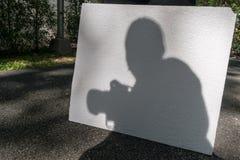 Schatten eines Fotografen, der Kamera hält Stockfotografie