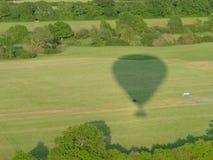 Schatten eines Heißluftballons auf einem grünen Feld stockfotografie