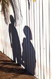 Schatten eines Jungen mit Mutter an einem hölzernen Zaun Lizenzfreies Stockbild
