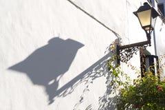 Schatten eines Laternenpfahls auf der Wand Stockbilder