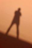 Schatten eines Mannes auf dem Sand Stockbild