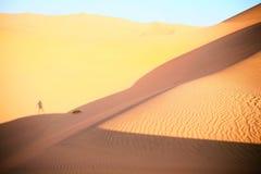 Schatten eines Mannes, der auf der Düne bleibt Lizenzfreie Stockbilder