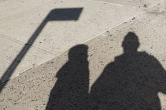 Schatten eines Vaters und seines Sohns auf einer rauen konkreten Straße lizenzfreie stockbilder