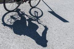 Schatten eines weiblichen Radfahrers Stockbilder