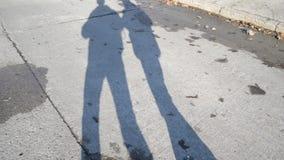 Schatten oder Schattenbilder von zwei gehenden Männern auf Betonplattestraße stock footage