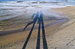 Schatten von den glücklichen Menschen, die auf einen Strand durch die Ostsee gehen Stockfoto