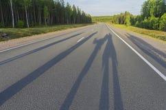 Schatten von einer Gruppe von Personen auf der Autobahn Stockbild