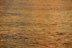 Schatten von gelb-orangeen Ozean-Wasserkräuselungen weg vom Nordufer Stockfoto