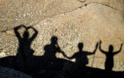 Schatten von glücklichen Menschen mit den Armen hoben auf Felsen an Lizenzfreie Stockfotografie